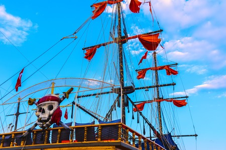 Masts and red sails of huge tourist ship decorated as pirate skull and crossbones in Alanya, Turkey