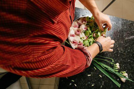 arrangment: Man making flowers arrangment orchids