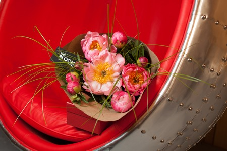 pion: bouquet of pink peonies on red-steel chair Stock Photo
