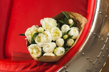 pion: Bouquet of white peonies on a red armchair with metal decoration