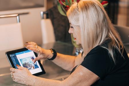 mujer sentada: mujer de 65-70 años de edad que usa el ordenador de la PC de la tableta del ipad en casa