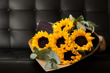 Deluxe bouquet of sunflowers on dark background