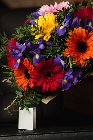 Flowers bouquet of gerbera, iris, and pistacia on dark background Reklamní fotografie