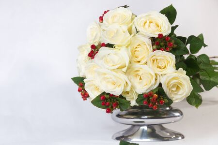 Bouquet of white roses with berries in the metal vase isolated on white background