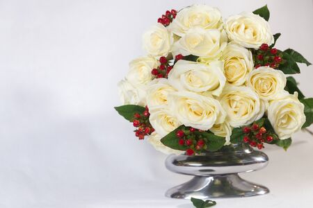 Isolated bouquet of white roses with red berries in a metal vase on the white background