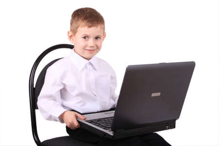 The boy of 5 years sits on a chair with a laptop Stock Photo - 2894829