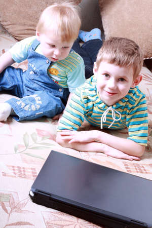 Two small boys together play near a laptop Stock Photo