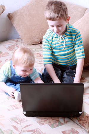 Two small boys together look at the screen of a laptop Stock Photo