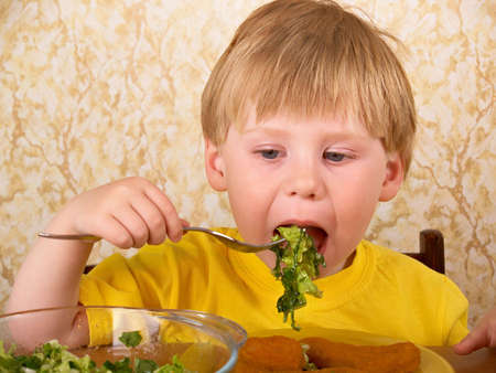 The little boy eats fresh salad
