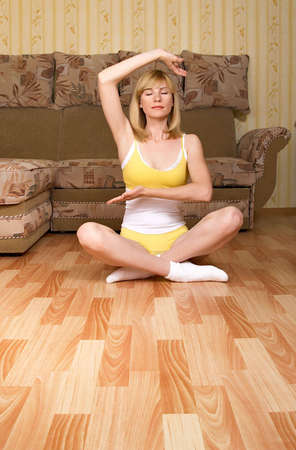 A beautiful young woman, meditating peacefully on the floor of her classy home. photo