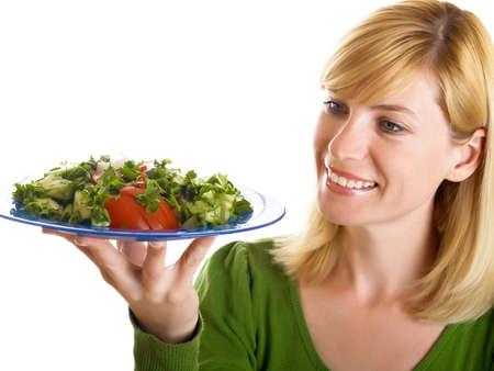 young woman holding in her hand a bowl of salad ïîèñê