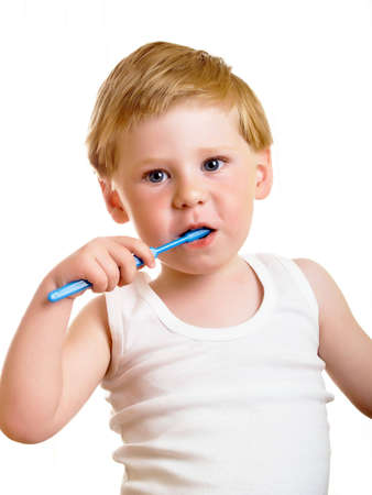 a beautiful little boy cleans your teeth on a white background