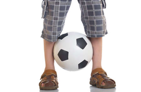 clamped: Football clamped between legs of the boy Stock Photo