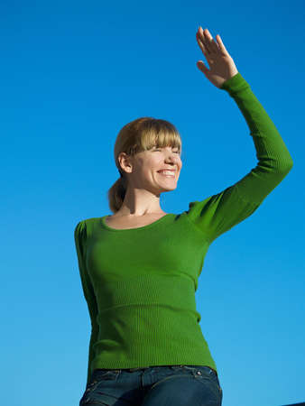 arched neck: Portrait of the young woman posing on a background of the dark blue sky