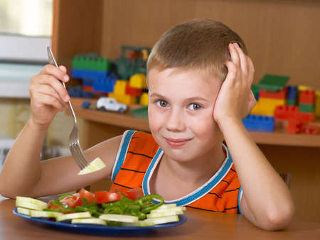 The little boy eats fresh salad on the table Stock Photo
