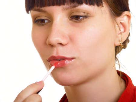 Beautiful young woman applying red lip gloss photo