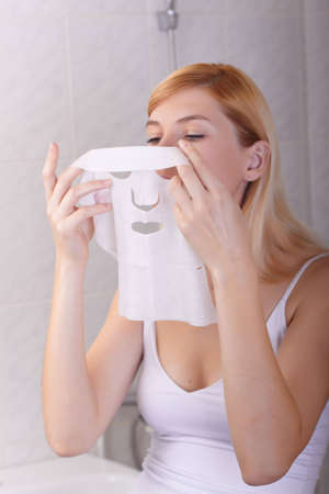 The young woman puts a nutritious mask for the person Stock Photo