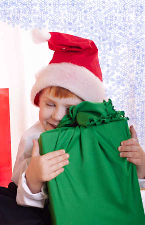 The little boy in a red cap with gifts photo