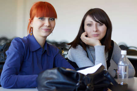 Two young students sit in for employment photo
