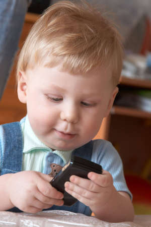 Portrait of the little boy with a mobile phone in hands photo