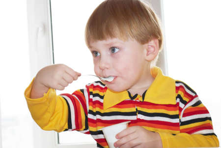 The little boy eats yoghurt behind a table