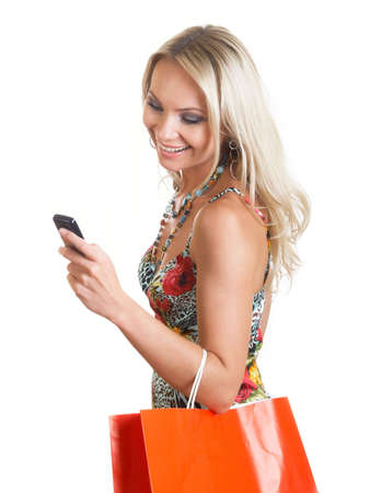 The young woman in elegant clothes looks at a mobile phone Stock Photo