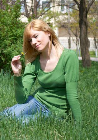 La joven mujer con una pequeña flor amarilla en una mano Foto de archivo - 6927742