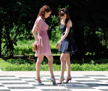 leggy girl: Two women cost on a chessboard in the summer Stock Photo