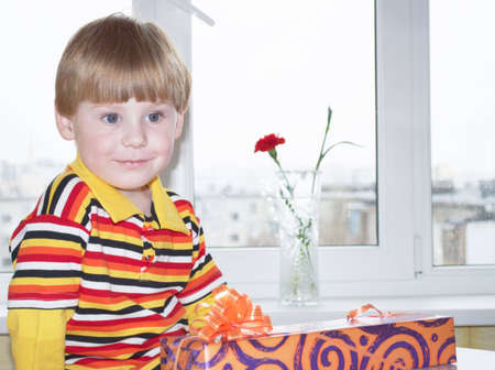 Portrait of the little boy with a gift box on a background