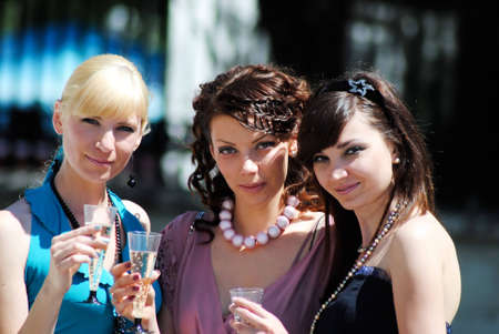 Three young women with glasses of a champagne in hands