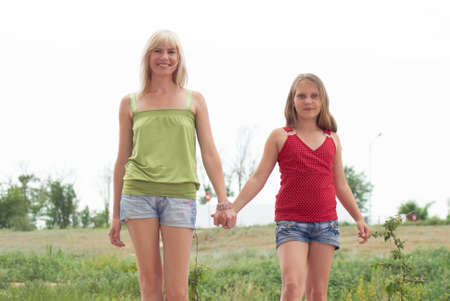 Mum with a daughter pose in the summer outdoor