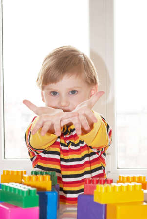 The beautiful little boy poses on a light background