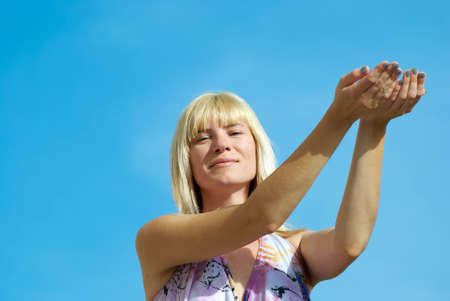 The young woman poses with the lifted hands on a background of the dark blue sky
