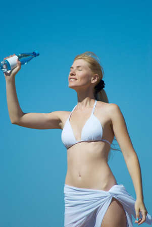 The woman in a bathing suit holds a bottle with water in the summer