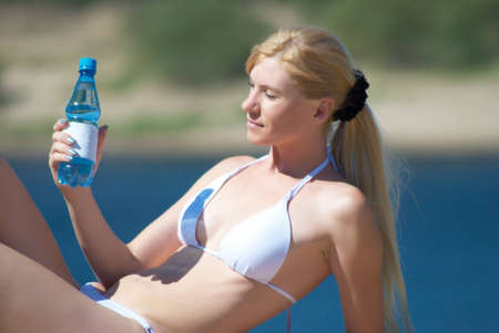 The woman in a bathing suit holds a bottle with water in the summer photo
