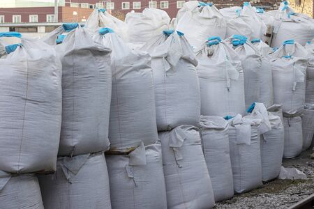 Large white bags with blue ribbon inside the salt lie on the street. Industrial fertilizers are stored in bags in a heap.