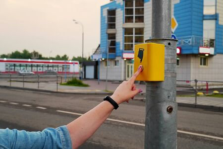 The hand of a girl with a clock presses the button of the pedestrian crossing. The button is lit in red, electronic pedestrian crossing. A hand sign indicates a button.