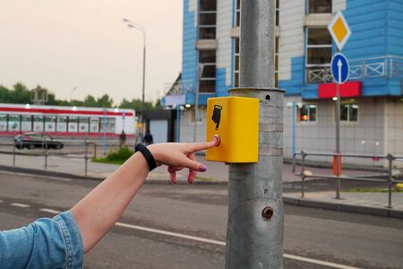 The hand of a girl with a clock presses the button of the pedestrian crossing. A hand sign indicates a button. The button is lit in red, modern electronic pedestrian crossing.