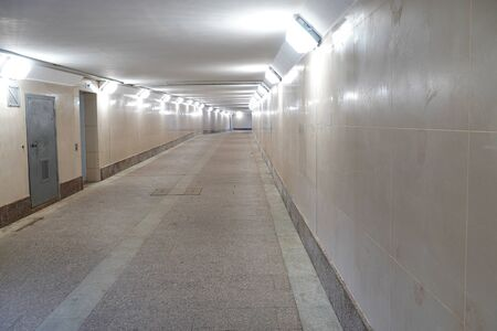 A pedestrian tunnel is empty without people. Underpass with light. Beige color.