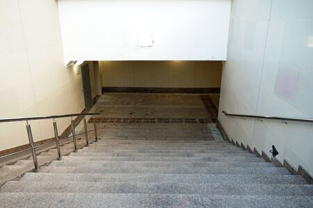Modern descent to the pedestrian tunnel is empty without people. Stairway down to the underground new passage. Beige color. Stock Photo