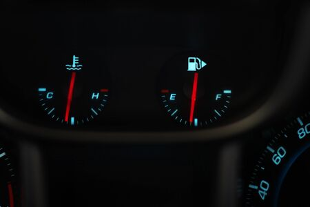 Car dashboard. Indicators of temperature and fuel level. Red arrows with blue values.