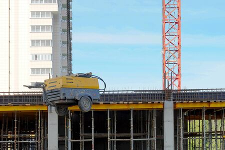 A construction crane lifts a welding machine. Chain slings hold equipment. Blue sky, high-rise building.