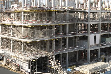 The construction of a multi-storey building. Construction iron scaffolding on several floors.