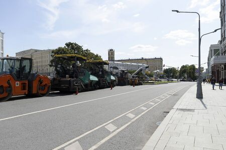 Russia, Moscow, 2019-08-10. Road equipment in a row stands on the road. The paver and the road roller rest before work. A simple technique. Preparation for repair of the roadway. Éditoriale