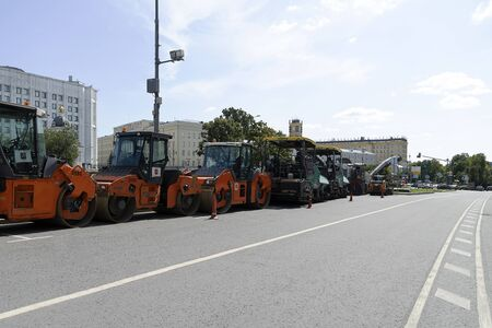 Russia, Moscow, 2019-08-10. Road equipment in a row stands on the road. Paver and road roller. Preparation for repair of the roadway. Éditoriale