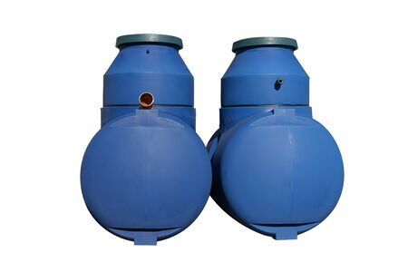 Blue plastic septic tanks stand in a row. Two cylindrical containers. Isolated background, a large barrel of sewage.