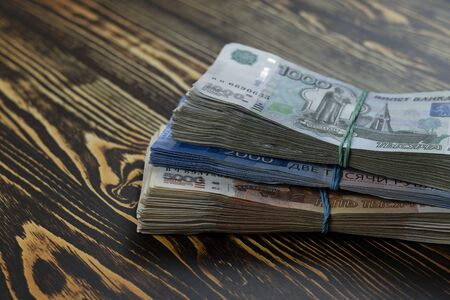 A bundle of Russian money in different denominations is tied with an elastic band. Five, two, one thousand rubles in banknotes, a large sum of money.