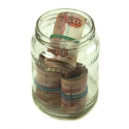 Russian money banknotes of five thousand rubles are rolled up and lie in a glass jar. Several packs of large rubles roll on a white background.