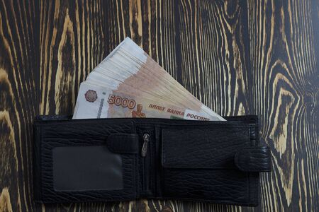 Cash five thousand Russian rubles bills, wooden background. A bundle of banknotes close-up in a mens wallet. A million rubles in your wallet.