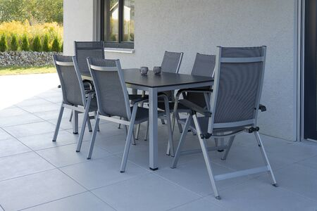 On the street terrace there are a gray table and six chairs made of metal and fabric, mounted on a tile. Beautiful modern romantic getaway. On the table are glass glasses for candles.